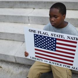 Lennos Lemon, 12, sits on the South Carolina Statehouse steps during a rally to take down the Confederate flag, Saturday, June 20, 2015, in Columbia, S.C. Rep. Doug Brannon, R-Landrum, said it's past time for the Confederate flag to be removed from South Carolina's Statehouse grounds after nine people were killed at the Emanuel A.M.E. Church shooting. (AP Photo/Rainier Ehrhardt)